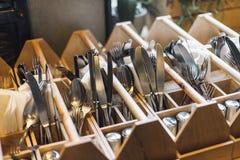 Gafflar, knivar och skedar i inre restauranger royaltyfria bilder