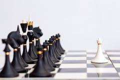 Gage blanc d'échecs devant les morceaux noirs Images stock