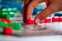Gage rouge sur un jeu de société avec la main Image stock