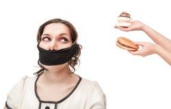 Gagged плюс женщина размера сокращанная с высококалорийной вредной пищей Стоковые Фото