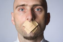 Gagged Man. A close up view of a man with tape across his mouth as if forbidden to speak Royalty Free Stock Photos