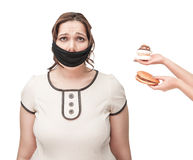 Gagged plus size woman seduced with junk food. Gagged beautiful brunette plus size woman seduced with junk food isolated royalty free stock photography
