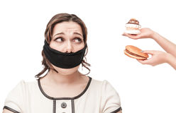 Gagged plus size woman seduced with junk food Stock Images