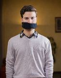 Gagged young man cannot speak Stock Photography
