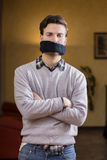 Gagged young man cannot speak Stock Photo