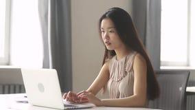 Gagnant asiatique enthousiaste de femme d'affaires célébrant la victoire en ligne regardant l'ordinateur portable clips vidéos