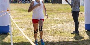 Gagnant de course de pays croisé avec la bande sur des genoux photos libres de droits