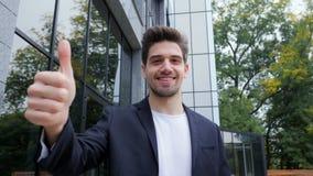 gagnant Réussite Le jeune homme de brune dans l'habillement d'affaires dans le secteur de bureau sourit à la caméra et renonce à  clips vidéos