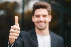 gagnant Réussite Le jeune homme de brune dans l'habillement d'affaires dans le secteur de bureau sourit à la caméra et renonce à  photo stock