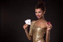 Gain de femme - la jeune femme dans une robe chique d'or tenant deux as et deux puces rouges, un tisonnier des as cardent la comb Photo stock