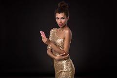 Gain de femme - la jeune femme dans une robe chique d'or tenant deux cartes, un tisonnier des as cardent la combinaison émotions Image stock