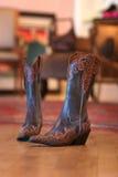 Gaines de cowboy de dames se reposant sur un étage en bois Photographie stock libre de droits