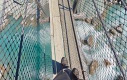 Gaines sur la passerelle d'oscillation au-dessus de l'eau blanche préoccupée Images libres de droits