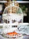 Gaiola de pássaro do vintage em um copo de água usado para a decoração e que recolhe envelopes imagens de stock royalty free