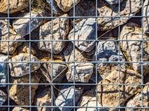 Gaiola que contém rochas e pedras com restos imagens de stock