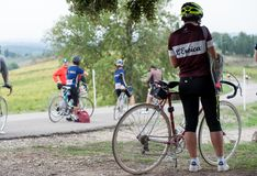 A young cyclist woman takes a break on the roadside, during a cy Stock Images