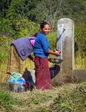 Women washing clothes at a public water tap in a small mountain village, Nepal royalty free stock images