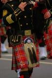 Gaitero en falda escocesa de la tela escocesa y túnica negra imagen de archivo