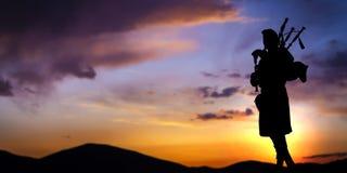 Gaitero escocés en la puesta del sol Fotos de archivo libres de regalías