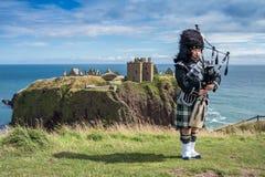 Gaitero escocés tradicional en código de vestimenta completo en el castillo de Dunnottar fotografía de archivo libre de regalías