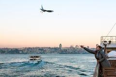 Gaivota de mar de alimentação da mulher da placa da balsa no nascer do sol foto de stock