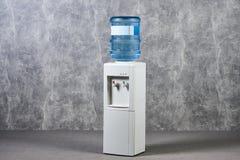 Galão do refrigerador de água branca no escritório contra a parede textured cinzenta b imagens de stock royalty free