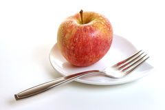 Gala apple on saucer. Details of a gala apple on a white saucer with a fork.  White background Stock Photography
