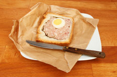 Gala pie on a table. Pork and egg gala pie in brown paper with a knife on a plate on a wooden tabletop Stock Images