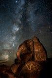 Galactic Petroglyphs. The Milky Way galaxy rises behind a rock covered with Native American petroglyphs, near Gila Bend, Arizona Stock Photography