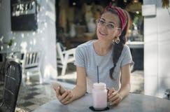 Galanteryjny model w czerwonych chustki na głowę i round szkłach pozuje z telefonem outdoors obraz royalty free