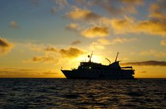 Galapagos Islands cruise ship in sunset royalty free stock photos