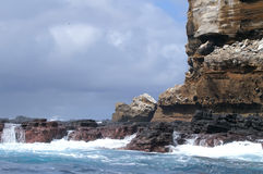 Galapagos islands and sea. Galapagos Islands rock cliffs and surf stock photo