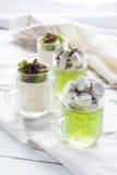 Galaretowacieje z kiwi owoc z marshmallows i kraciastą czekoladą w szkle, pokrojony kiwi na białym drewnianym stole Zdjęcie Royalty Free