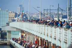 Galata bridge with fishermen angling from it. Istanbul,Turkey - May 01, 2015: Galata bridge with fishermen angling from it and crowds of tourists Royalty Free Stock Photos