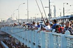 Galata Bridge. ISTANBUL - MAY 2: Fishermen on the famous Galata Bridge on May 2, 2013 in Istanbul stock photo