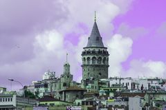 Galata Tower of Istanbul City Purple filter. Frontal view of Galata Tower and Cityscape of Istanbul with a purple filter applied.  Bustling city in Turkey that Royalty Free Stock Photo