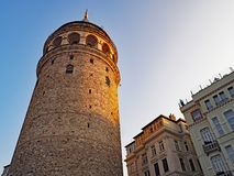 The Galata Tower lit by the setting sun in Istanbul, Turkey. The Galata Tower in the city of Istanbul Turkey is lit by the setting sun Stock Images