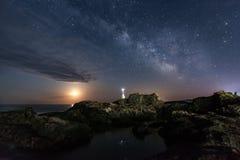 Galaxen och månen över fyren Arkivfoton