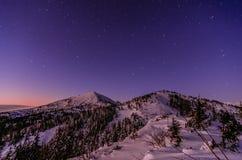 Galaxia de la vía láctea Estrellas púrpuras del cielo nocturno sobre las montañas Fotografía de archivo libre de regalías