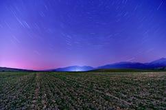 Galaxia de la vía láctea Estrellas púrpuras del cielo nocturno sobre las montañas Fotografía de archivo