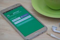 Galaxie J7 de Samsung avec l'application de TripAdvisor sur l'écran tactile sur la table en bois Photos stock