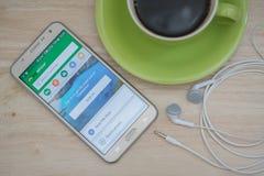 Galaxie J7 de Samsung avec l'application de TripAdvisor sur l'écran tactile sur la table en bois Photo libre de droits