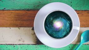 Galaxy in coffee cup. Animation Rotating spiral galaxy in coffee cup on wooden table stock footage