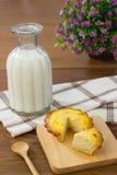 Galdéria lascada do queijo com garrafa de leite foto de stock