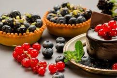 Galdérias com mirtilos, os corintos vermelhos e o chocolate na tabela Foto de Stock