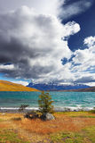 The gale on Lake Laguna Azul. A huge cloud covers the sky. In the distance the mountains with snow-capped Stock Image