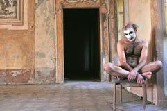 Galen man som är naken i ett övergett hus i Italien