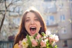 Galen och lycklig ung flicka som ser kameran med lycka och sinnesrörelser i hennes ögon som rymmer en stor bukett av arkivfoton