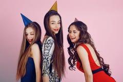 Galen partitid av tre härliga stilfulla kvinnor i elegant aftondräkt som firar och att ha gyckel som dansar leende Arkivfoton