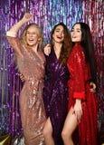 Galen partitid av tre härliga stilfulla kvinnor i elegant dräkt som firar nytt år, födelsedag och att ha gyckel, dans royaltyfri bild
